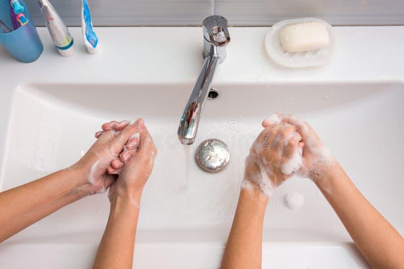两人洗他们的在水槽的手,顶视图 免版税库存图片