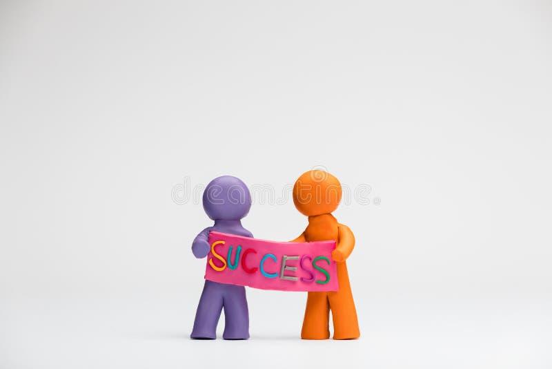 两人由拿着与词成功的彩色塑泥做了一张海报写对此,在白色背景,被排列在中心 免版税库存照片