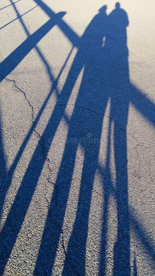 两人的被延长的阴影具体街道表面上的,在一个非常晴朗的夏日 库存照片