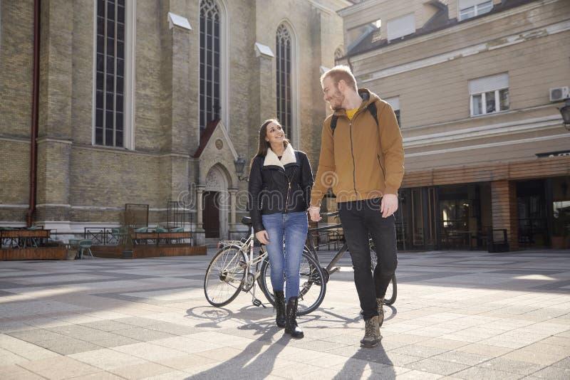 两人-夫妇,微笑对彼此,当握手,看起来面对面时 走在一个美好的城市广场在欧洲 库存照片