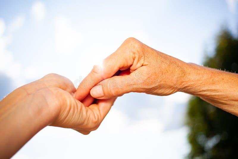 两代之间的亲密姿态 年轻女人与一位高级女士握手 蓝天背景 免版税库存照片