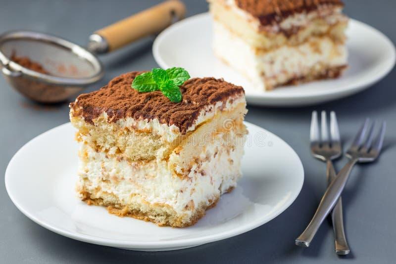 两件在一块白色板材的传统意大利提拉米苏点心蛋糕,用可可粉和薄菏装饰,在灰色 免版税库存图片