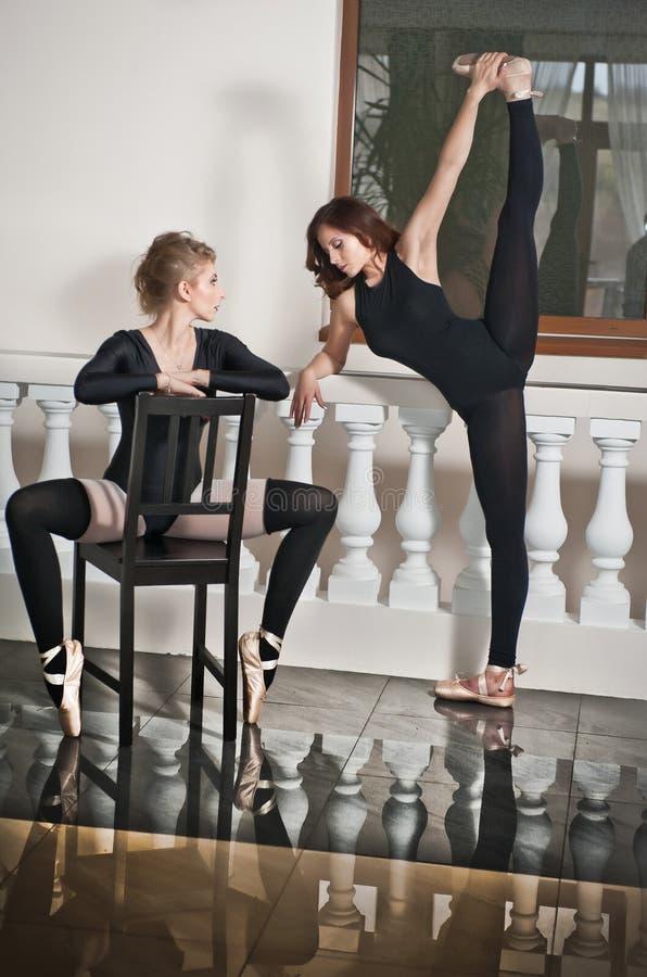 两位优美的芭蕾舞女演员,一做分裂的和一坐椅子,在大理石地板上 华美的跳芭蕾舞者 库存照片