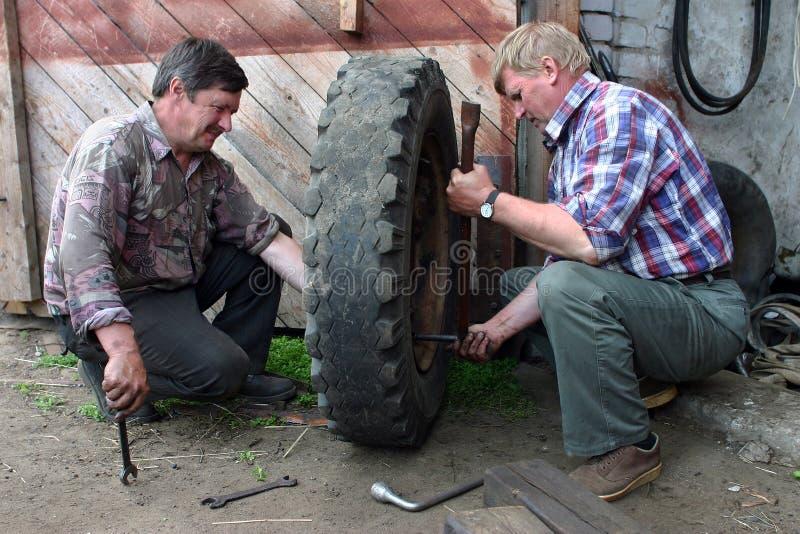 两位俄国农夫修理把疆土农厂车库引入 库存照片