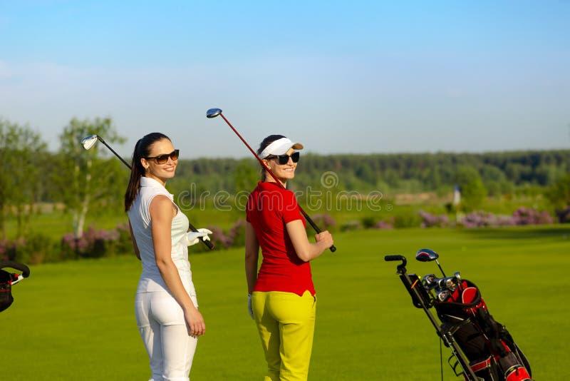 两位俏丽的女子高尔夫球运动员走和谈话在高尔夫球场 免版税库存图片
