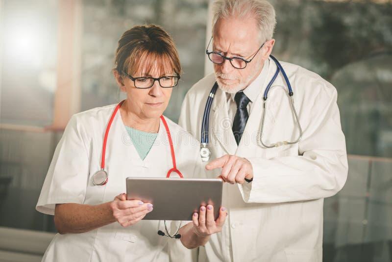 两位医生谈论关于关于片剂的医疗报告 库存图片