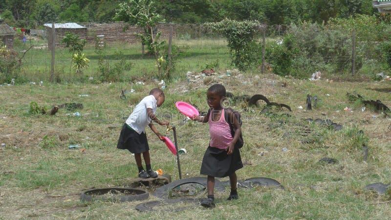 两位南非女小学生漂净他们的使用的板材吃完午饭 免版税库存图片