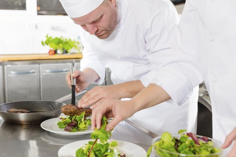 两位厨师在食家餐馆准备牛排盘 免版税图库摄影