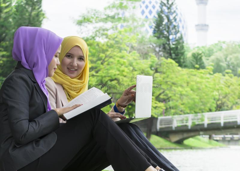 两位大学生有讨论和改变想法,当坐在公园时 免版税库存照片