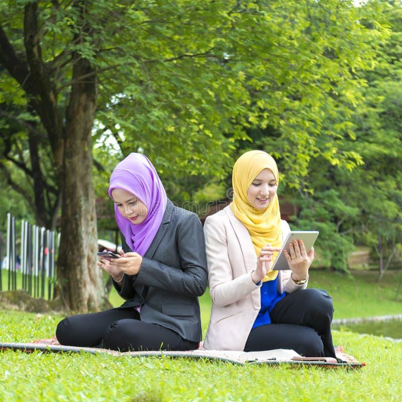 两位大学生繁忙发短信与他们的智能手机,当休息在公园时 免版税库存图片