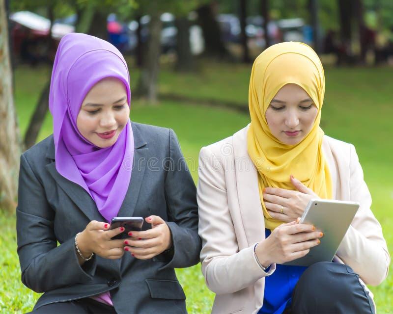 两位大学生繁忙发短信与他们的智能手机,当休息在公园时 免版税库存照片