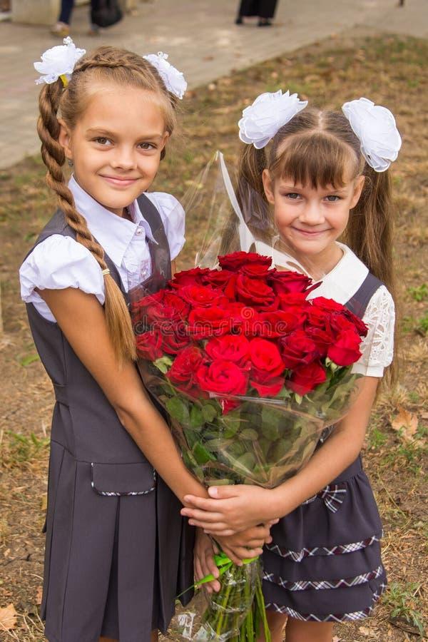 两位女小学生在他们的手上拿着一大花束 图库摄影
