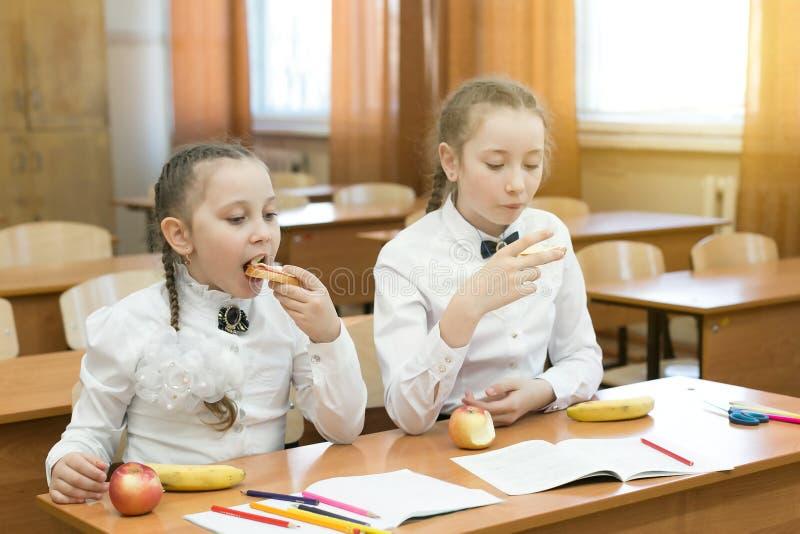 两位女小学生在长凳吃在教室 免版税图库摄影