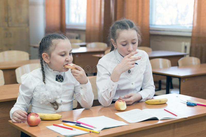 两位女小学生在长凳吃在教室 库存图片