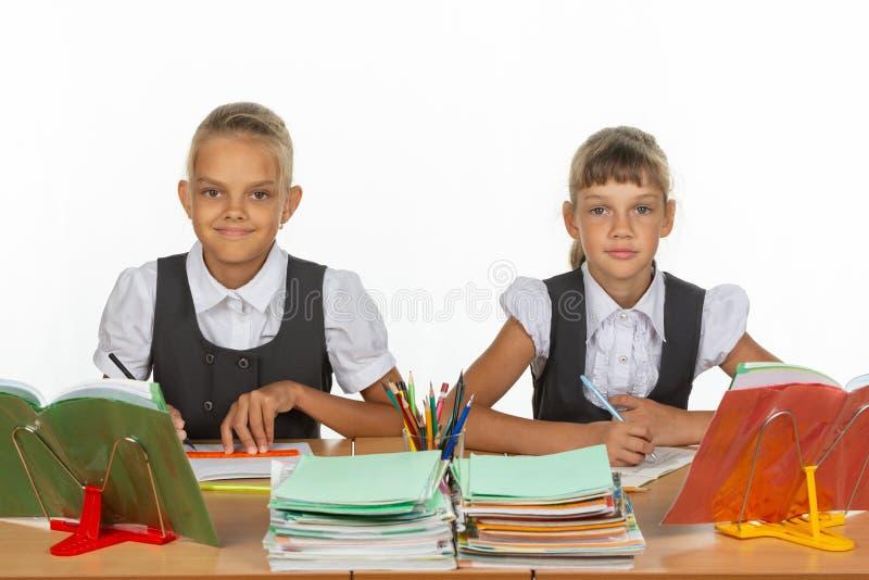 两位女小学生注视专心地和无感情入框架 免版税库存照片