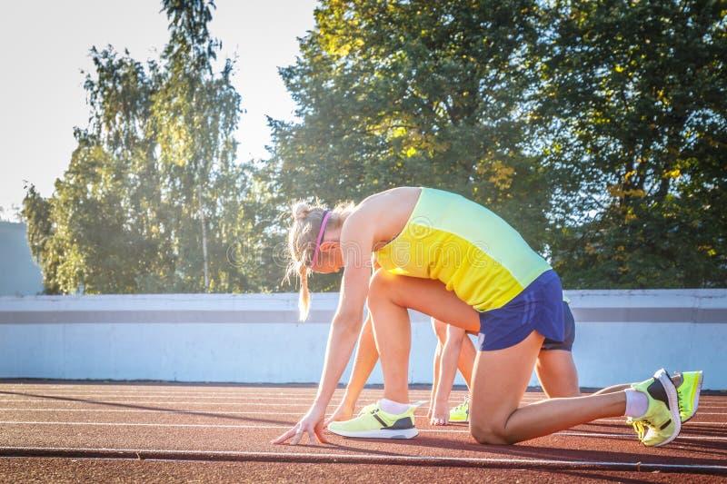 两位女性准备好短跑选手的运动员开始在一条红色连续轨道的种族在竞技体育场内 库存照片