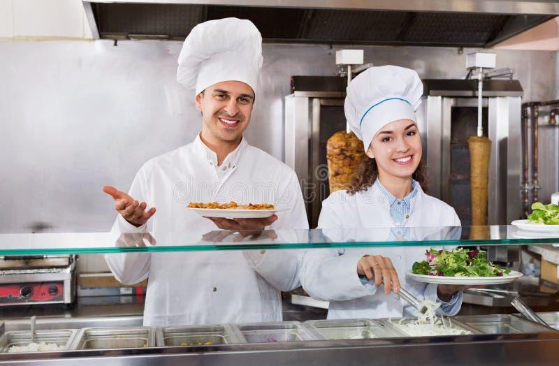 两位好客的厨师画象有kebab的在快餐地方 免版税库存图片