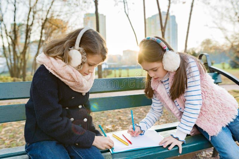 两位小俏丽的艺术家画与色的铅笔的,女孩坐一条长凳在晴朗的秋天公园 免版税库存图片