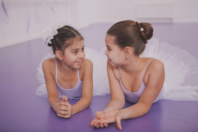 两位小芭蕾舞女演员谈话在舞蹈课以后 免版税库存图片