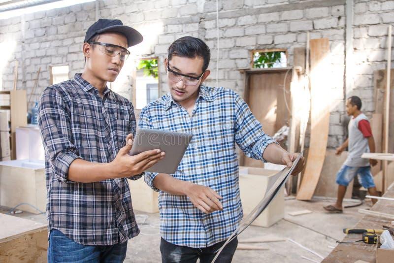 两位年轻木匠谈论关于家具材料 免版税图库摄影