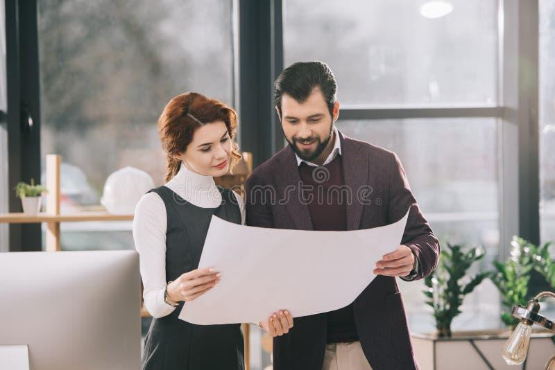 两位建筑师与图纸一起使用 免版税图库摄影
