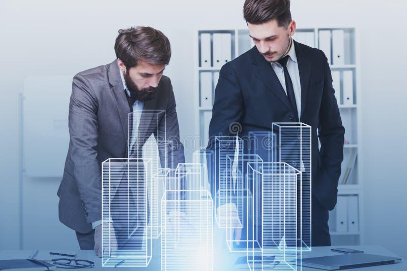 两位建筑师与城市全息图一起使用 免版税库存图片