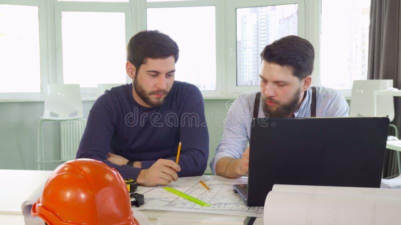 两位建筑师姿态在桌上 免版税库存图片