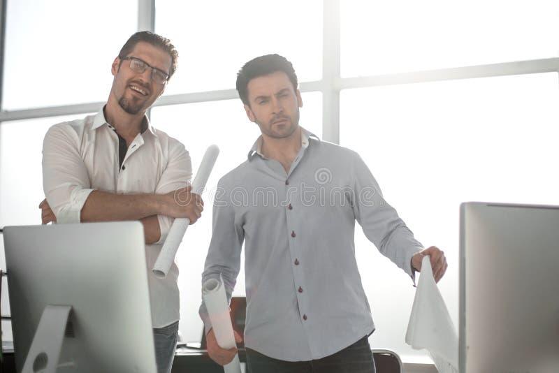 两位建筑师谈话,当站立在设计事务所时 免版税库存图片
