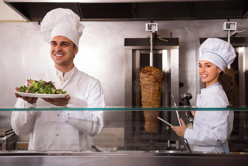 两位微笑的厨师画象有kebab的 库存图片