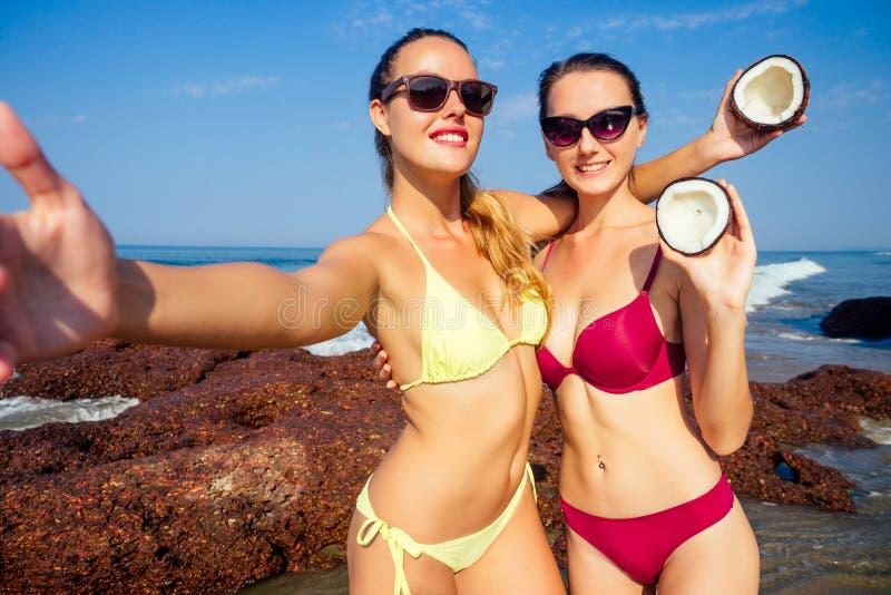 两位性感的年轻女性穿着时尚的比基尼泳衣,在海洋热带天堂海岸上举着椰子 完美 免版税库存图片