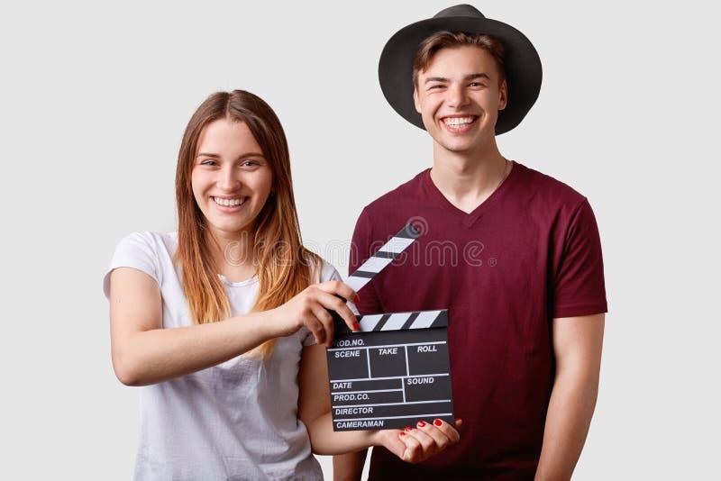 两位成功的年轻女性和男性著名生产商或主任拿着影片拍板,参加射击影片,有快乐前 免版税库存照片
