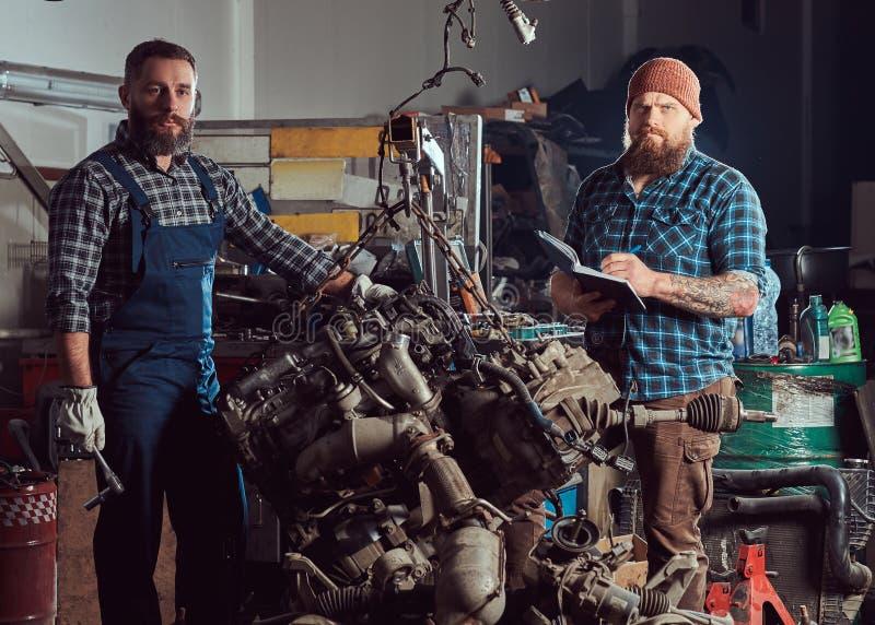 两位有胡子的技工专家修理在车库的液压悬挂被上升的发动机 库存照片