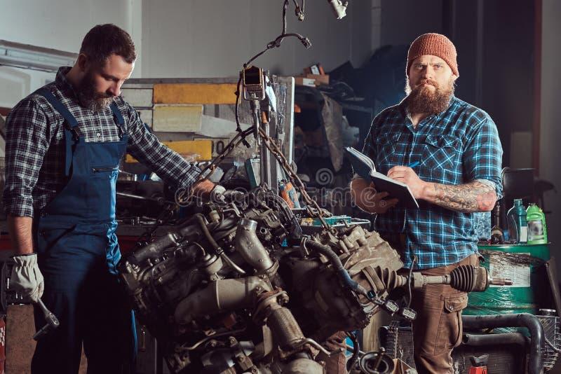 两位有胡子的技工专家修理在车库的液压悬挂被上升的发动机 免版税库存图片