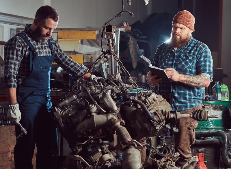 两位有胡子的技工专家修理在车库的液压悬挂被上升的发动机 库存图片