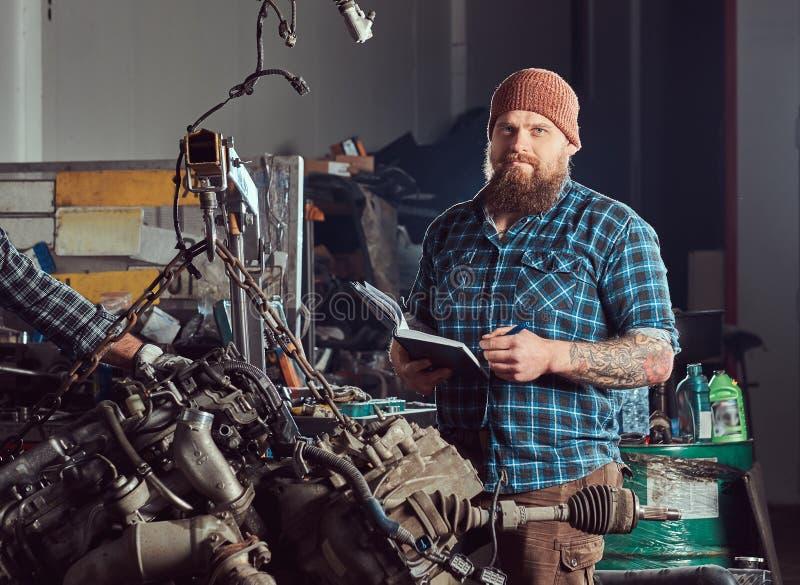 两位有胡子的技工专家修理在车库的液压悬挂被上升的发动机 免版税库存照片