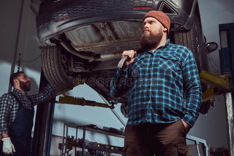 两位有胡子的残酷技工修理在一种推力的一辆汽车在车库 免版税库存图片