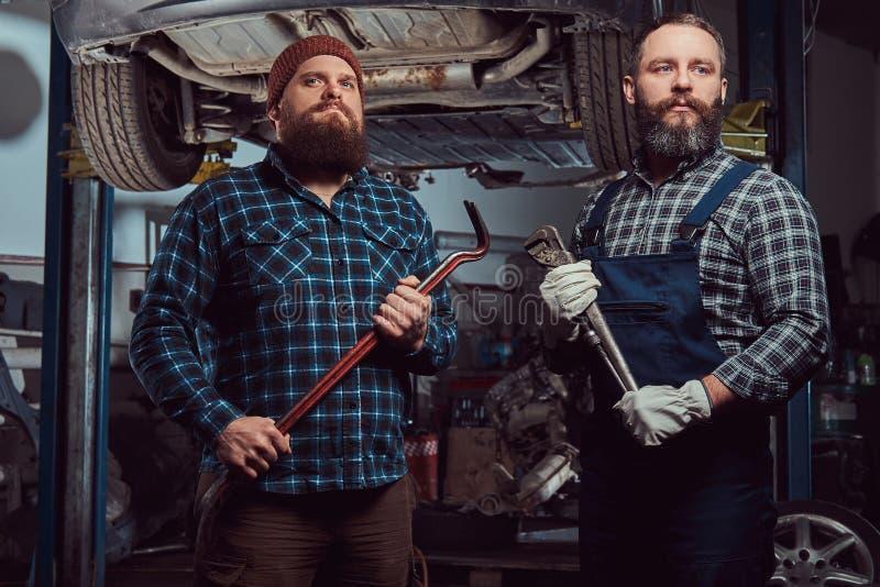 两位有胡子的残酷技工修理在一种推力的一辆汽车在车库 库存照片