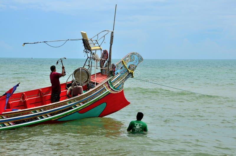 两位泰国渔夫准备有船锚的小船在海边北大年泰国 库存照片