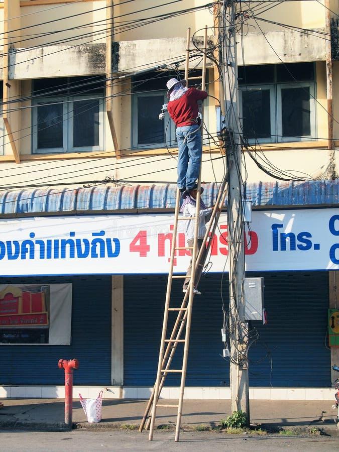 两位泰国电工修理在杆的混乱的电线 库存照片