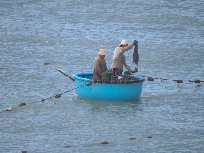 两位渔夫在一条传统越南小船航行 他们中的一个投掷网 免版税库存图片