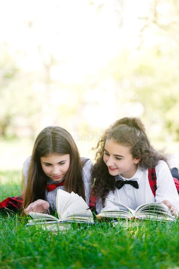 两位滑稽的女小学生在草和看书说谎 女孩,女朋友,姐妹被教教训本质上 免版税库存图片
