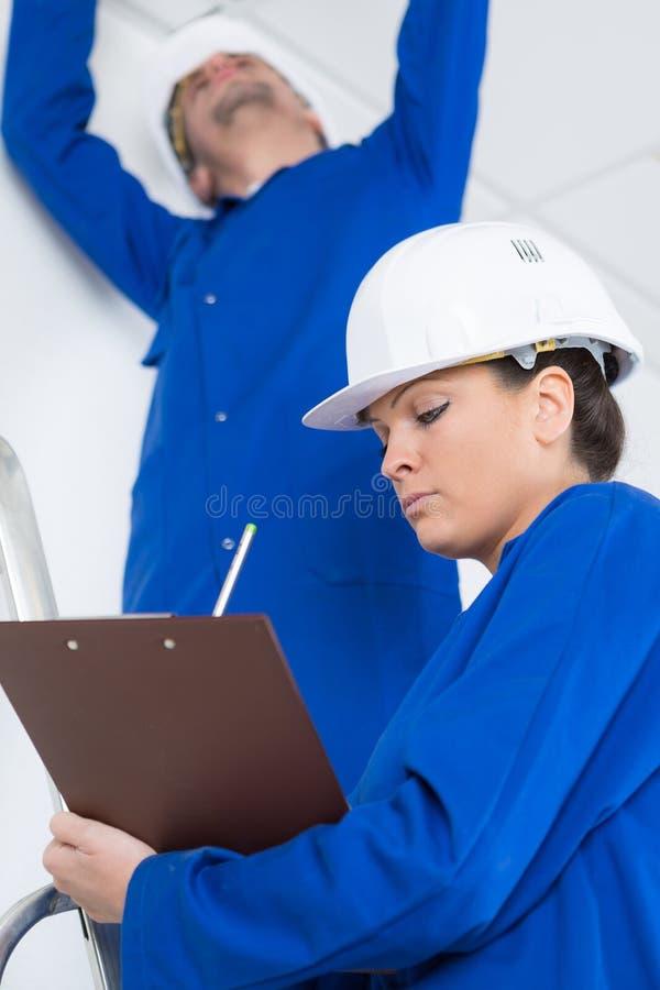 两位电工在屋子里建设中 库存图片