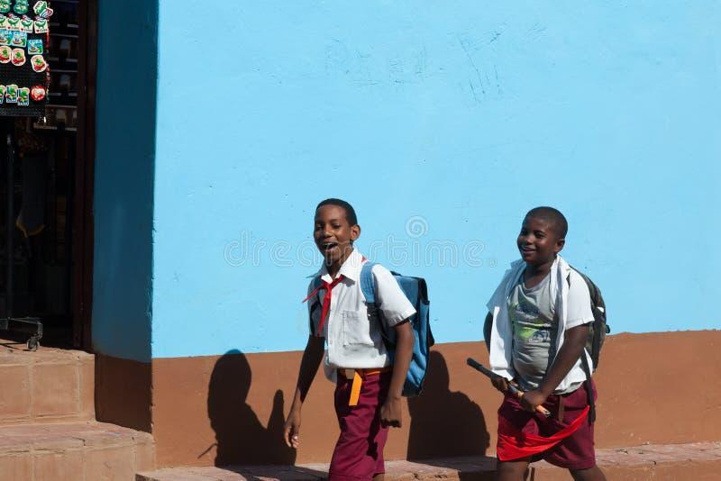 两位男小学生在Th街道上走在古巴在镇特立尼达里 孩子有红色先驱领带 免版税库存图片