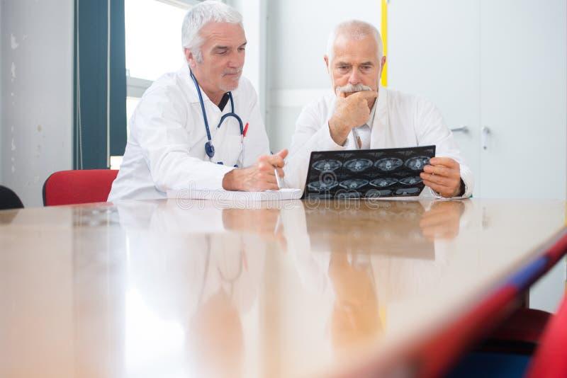 两位男性医生谈论X-射线在桌上 免版税库存照片