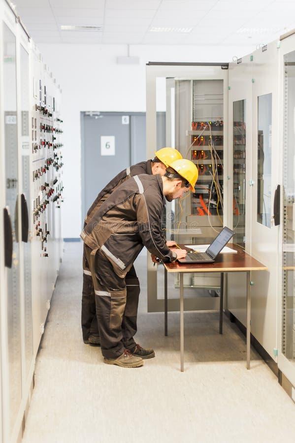 两位维护工程师检查中转与l的安全系统 库存照片