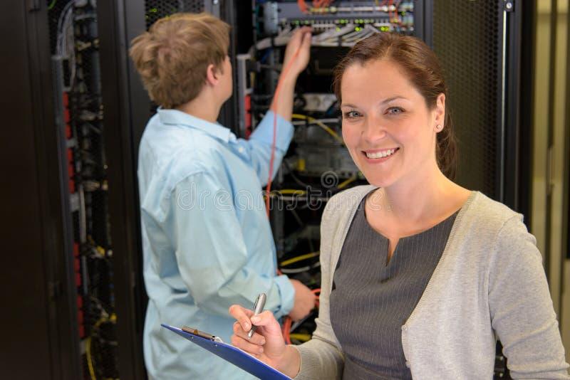 两位网络工程师在服务器屋子里 免版税库存图片