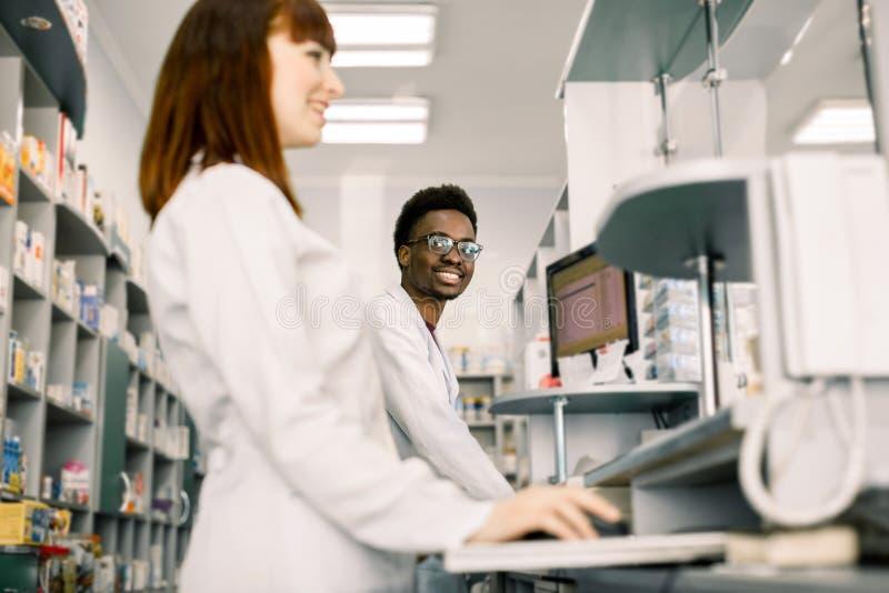 两位药剂师一起检查关于医学的男人和妇女信息在计算机上,现代药房 库存图片
