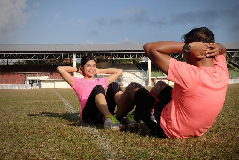 两位运动员在穿橙色和桃红色衬衣的一好日子一起咬嚼 他们在橄榄球的草行使 库存照片