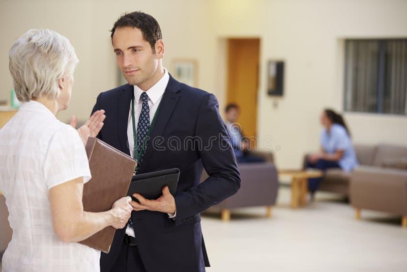 两位顾问谈论耐心笔记在医院 库存照片