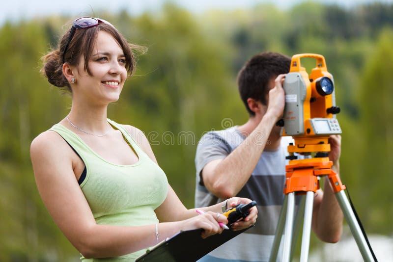两位年轻土地测量员 库存照片